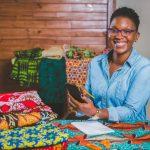 Diseñadora afroamericana en su oficina con muestras de telas coloridas sobre la mesa. Concepto: Ideas creativas para negocios