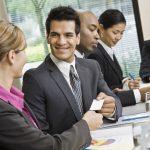 Dueño de una empresa compartiendo su tarjeta de negocios con un cliente durante una junta en su oficina. Concepto: tarjetas de negocios.