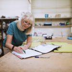 Empresaria trabajando sobre mesa en papeleo en su taller. Concepto: Pronóstico de flujo de efectivo
