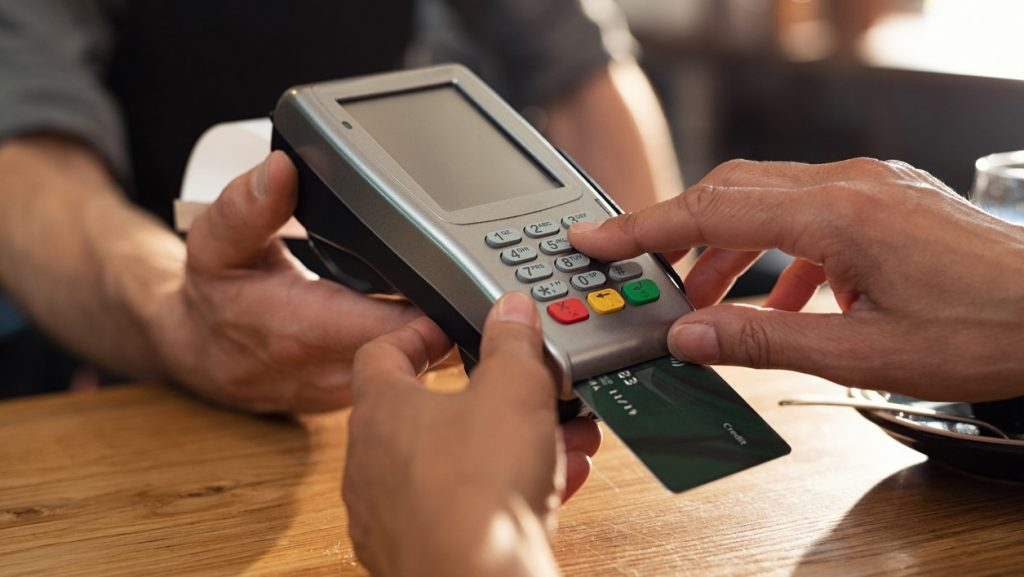 Closeup of hand using credit card swiping machine to pay. Female hand with credit card paying through terminal for payment in coffee shop. Woman entering debit card code in swipe machine. concept: best credit card processing