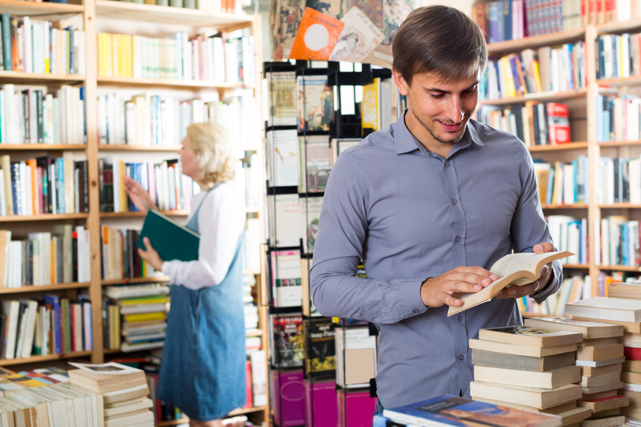 Young man looking at open book in bookstore. Concept: Best Business Books.
