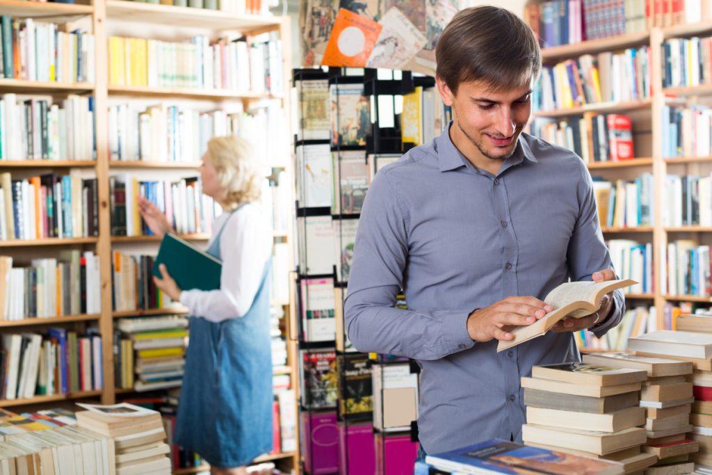 Hombre joven ojeando libro en librería. Concepto: Los mejores libros de negocios