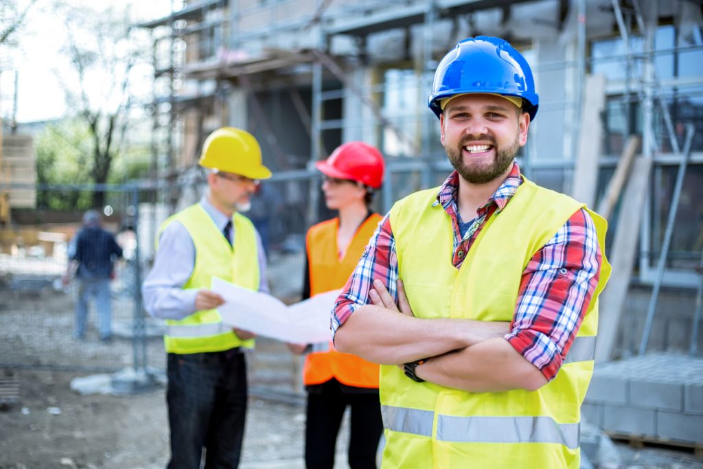 Construction business owner in construction site with crew in the background. Concept: how to improve cash flow in your construction business