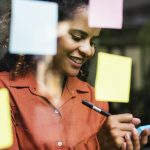 Female business owner using sticky notes on window to brainstorm business names ideas