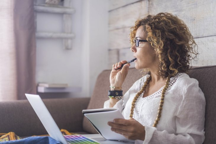 Business owner with writer's block trying to figure out what she's going to write about in her business blog. Concept: What should you write aboout in your business blog