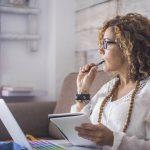 Dueña de una empresa con bloqueo creativo trata de pensar en temas para escribir en su blog para empresas. Concept: ¿Sobre qué deberías escribir en el blog de tu negocio?