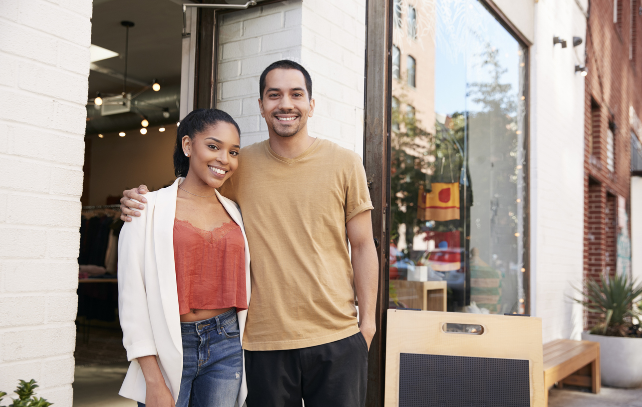 Young latino couple smiling outside their business that is now protected thanks to commercial insurance. Concept: best small business insurances