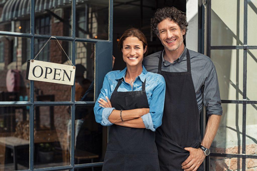 Pareja de dueños de restaurante a la puerta del establecimiento con señal de abierto. Concepto: Cómo registrar el nombre de tu negocio