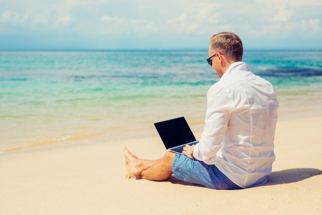 Empresario joven usando computadora en la playa en el verano. Concept: Ideas para negocios de verano
