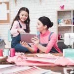 Mamá empresaria e hija mirando tablet en taller de costura. Concepto: mamá empresaria.