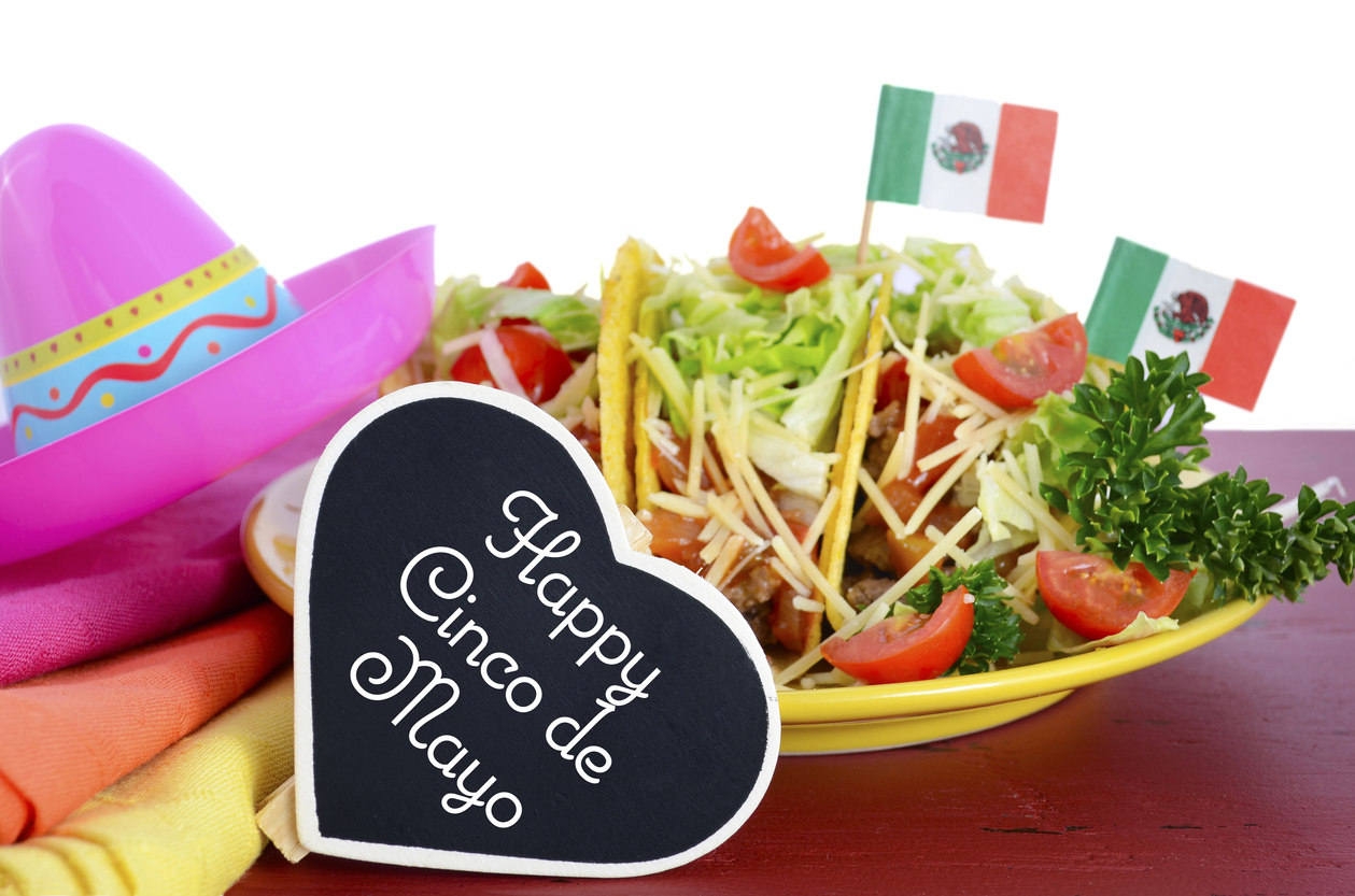 Happy Cinco de Mayo bright colorful party food with platter of tacos on red wood table. Concept: Cinco de Mayo menu and Cinco de mayo ideas