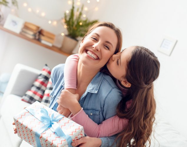 Young woman and girl at home celebrating mother's day sitting on sofa daughter hugging mother kissing cheek mom laughing joyful holding gift box. Concept: Mother's Day ideas