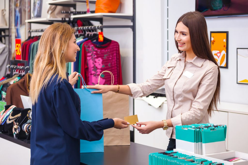 Shoper at clothing store giving her credit card to seller. Concept: spring sale