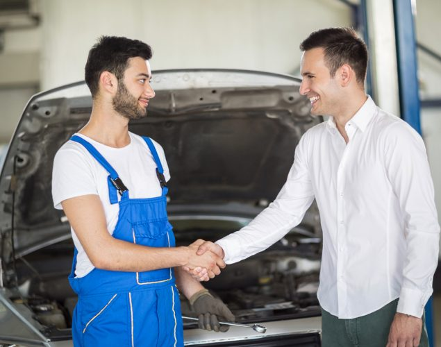 Smiling client and mechanic shaking hands in sevice. Concept: customer financing