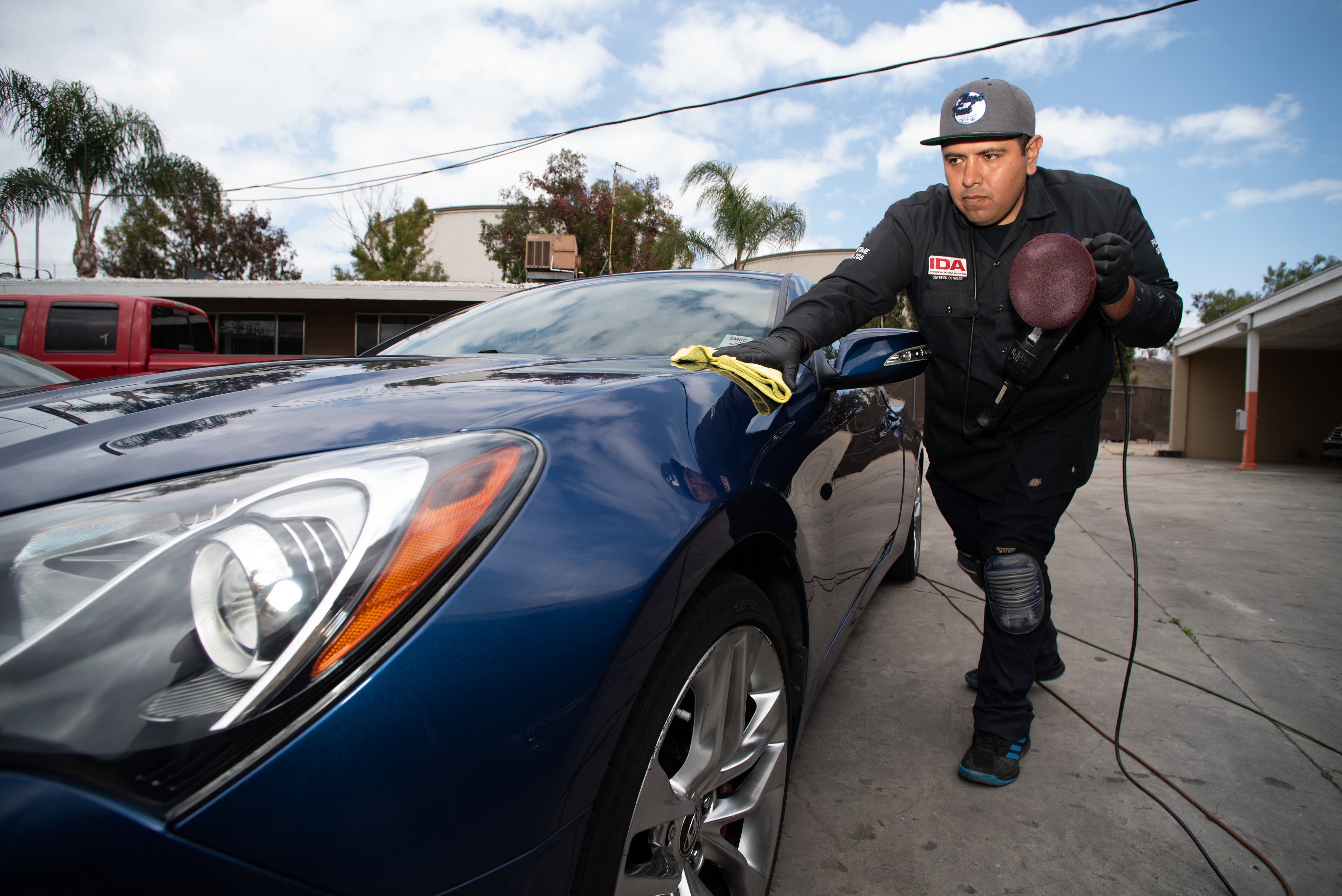 Ángel Rojas working on a car for his detail service businessin Los Angeles. Concept: Success Story: Ángel Rojas, Security and Efficiency Above All