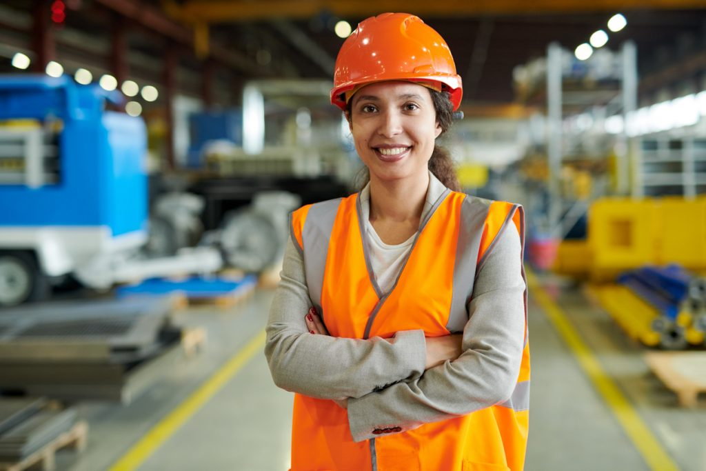 Cheerful latino woman wearing hardhat smiling happily looking at camera while posing confidently in her construction business. Concept: how to get a business loan for your construction business