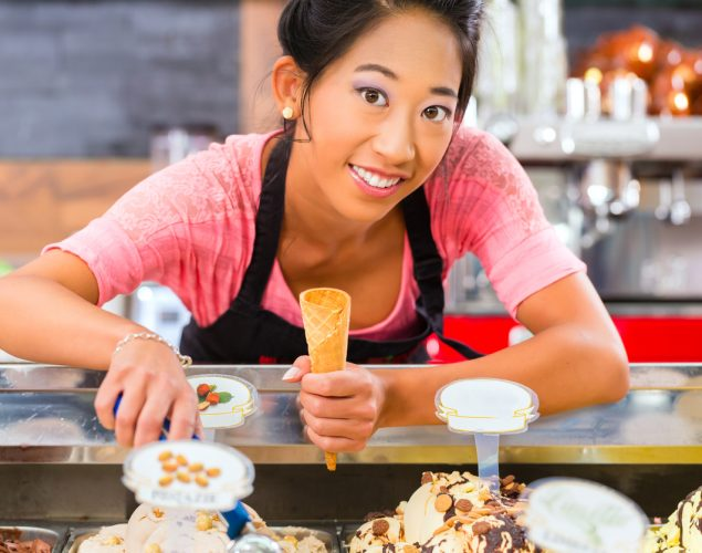 Young Asian saleswoman in an ice cream parlor takes a scoop of ice cream. Concept: How to hire employees in peak season