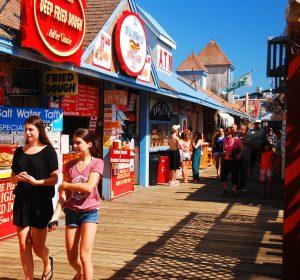 People on boardwalk during summertime. Concept: summer sales