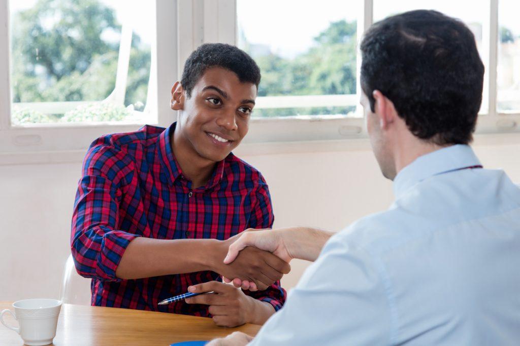 Pasante afroamericano dando un apretón de manos después de una entrevista para el programa de pasantías en las oficinas de un pequeño negocio. Concept: Por qué y cómo ofrecer pasantías en tu pequeña empresa