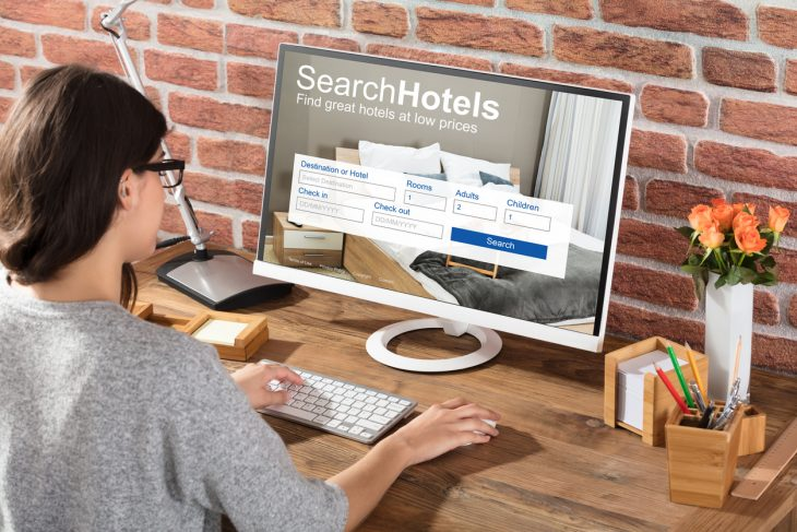 Close-up Of A Woman Searching Hotels Online On Computer. Concept: Online booking software