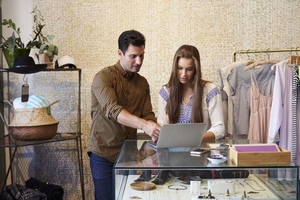 Man and woman, owners of clothes shop in front of computer. Concept: online lenders vs Camino Financial