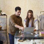 Hombre y mujer, dueños de tienda de ropa, frente a computadora. Concepto: Prestamistas en línea y Camino Financial