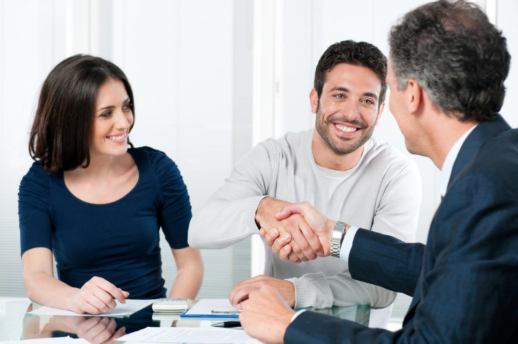 Couple meeting in bank with bank representative. Concept: All you need to apply for a small business loan.