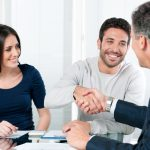 Pareja reunida con representante de banco en sucursal. Concepto: Todo lo que necesitas saber para solicitar un préstamo comercial.