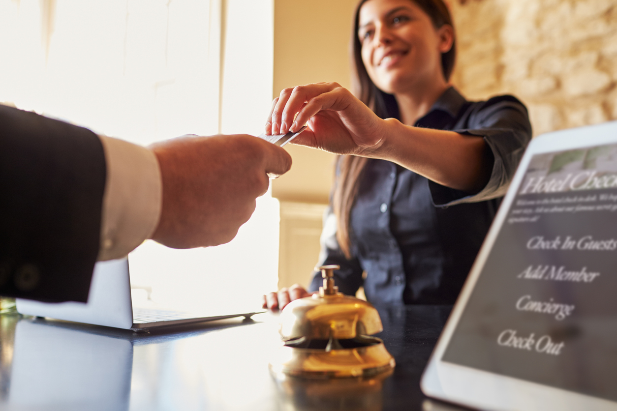 Guest takes room key card at check-in desk of hotel, close up. Concept: how to get a business loan for your hospitality business
