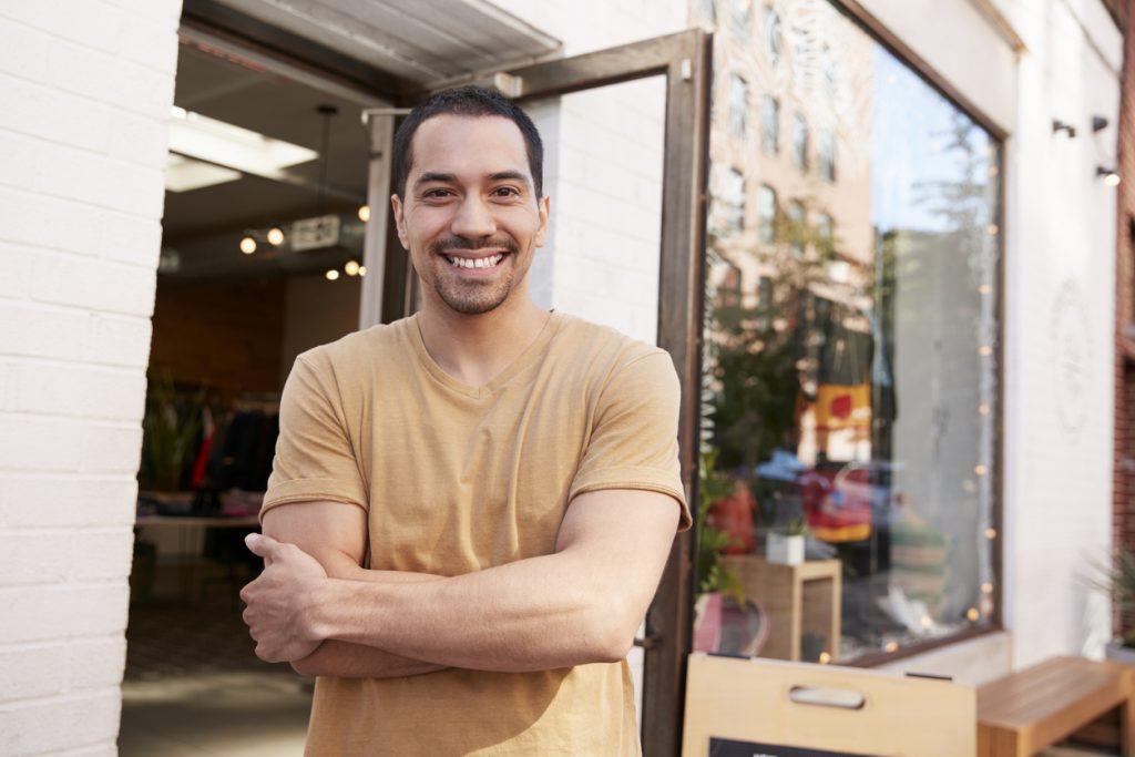 Joven empesario latino a la puerta de su negocio. Camino Financial no requiere un Número de Seguro Social