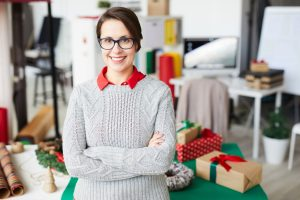 Young smiling businesswoman in studio with packages in the background during winter season. Concept: Low season survival of your small business