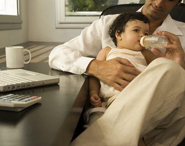 Father feeding baby in his office.Concept: Balancing fatherhood and business.