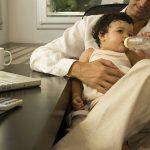 Padre alimentando a su bebé en la oficina. Concept: Logra un balance perfecto entre la paternidad y los negocios