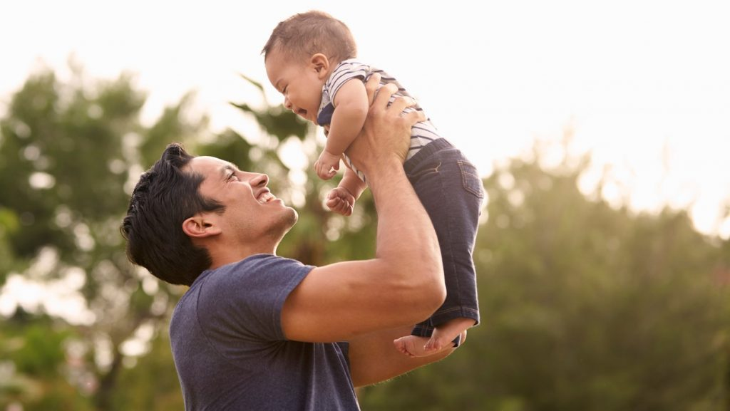 Millennial Hispanic father holding his little baby in the air in the park, close up