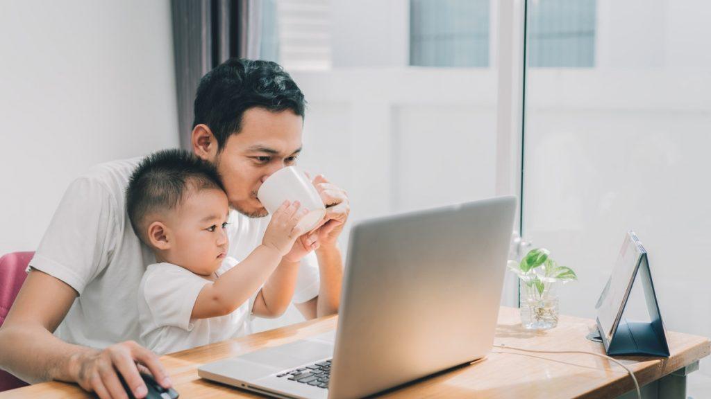 Hijo asíatico ayudándole a su papá a tomar café mientras trabaja en su laptop. Home office, trabajando desde casa.