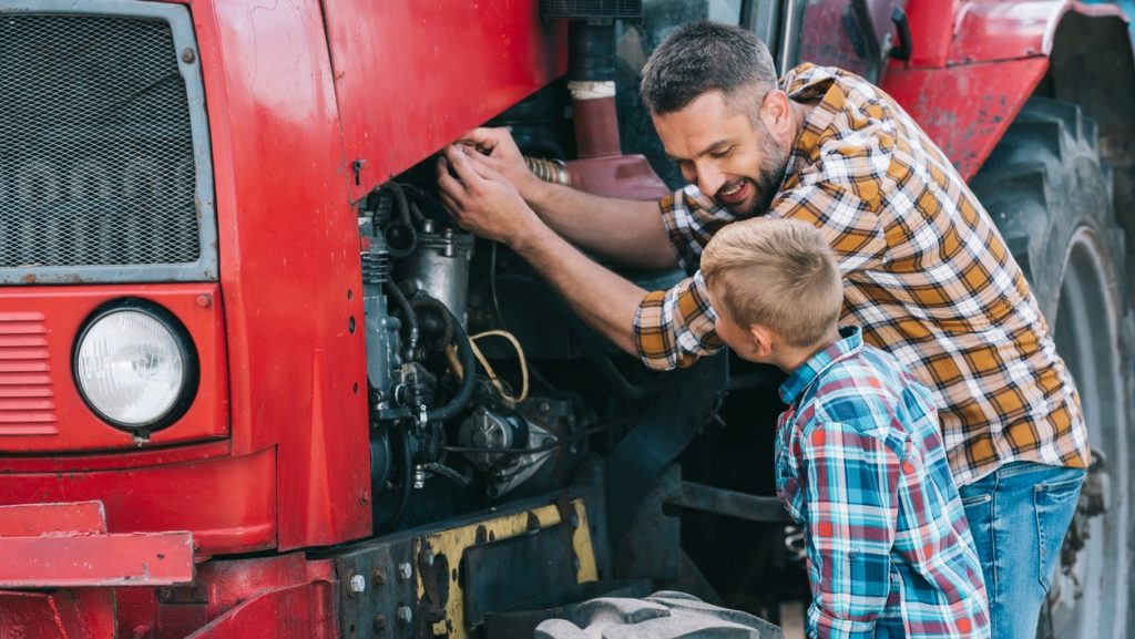 Padre e hijo felices trabajando en el motor de un camión.