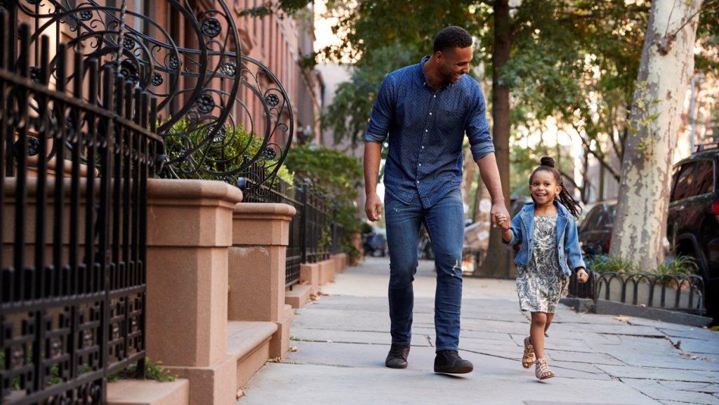 Padre e hija caminando por la calle platicando y riendo.