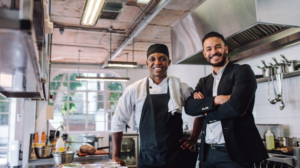 Portrait of restaurant owner with chef in kitchen. Businessman with professional cook standing together and looking at camera. concept: food truck
