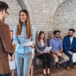 Hombre en oficina dandole la mano a una chica lista para su entrevista en una oficina moderna. Concept: Cómo contratar estudiantes para tu pequeña empresa