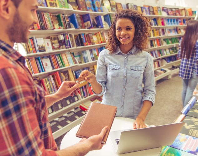 Female student at bookstore buying a book and paying with credit card. Concept: student discounts