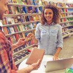Estudiante en librería comprando un libro y pagando con tarjeta de crédito. Concepto: descuentos para estudiantes