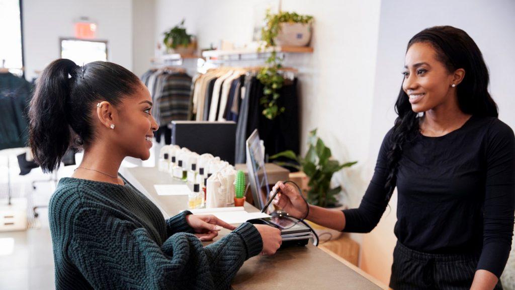 Mujer haciendo pago con tarjeta de crédito en una tienda de ropa. concept: apoya a las pequeñas empresas