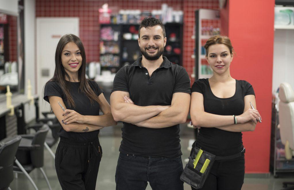 Tres empleados de peluquería en uniforme posando frente a cámara. Concepto: Micropréstamos y líneas de crédito: diferencias.