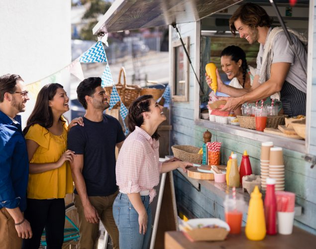 Smiling waiter giving order to customers at counter in food truck van. Concept: how to expand your food truck business