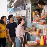 Cocinero sonriente entregando su orden a una clienta en su food truck. Concept: cómo expandir tu food truck