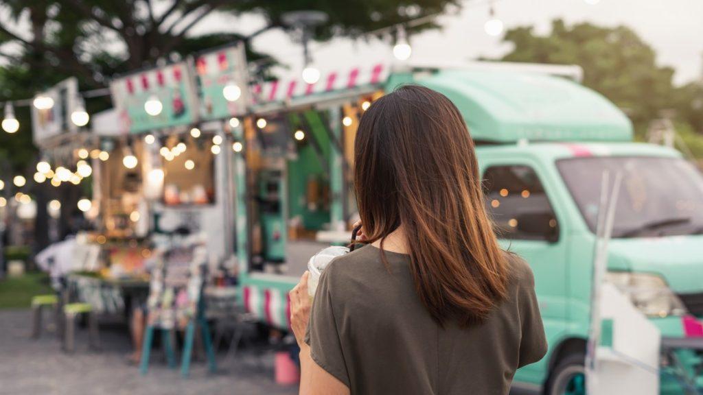 Mujer joven caminando hacia food truck. Concept: cómo expandir tu food truck