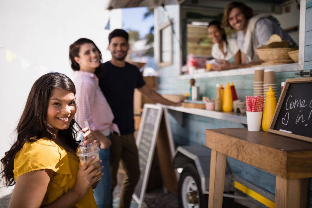 Retrato de amigos sonriendo mientras compran comida en un food truck. Concept: cómo empezar un food truck para expandir tu restaurante