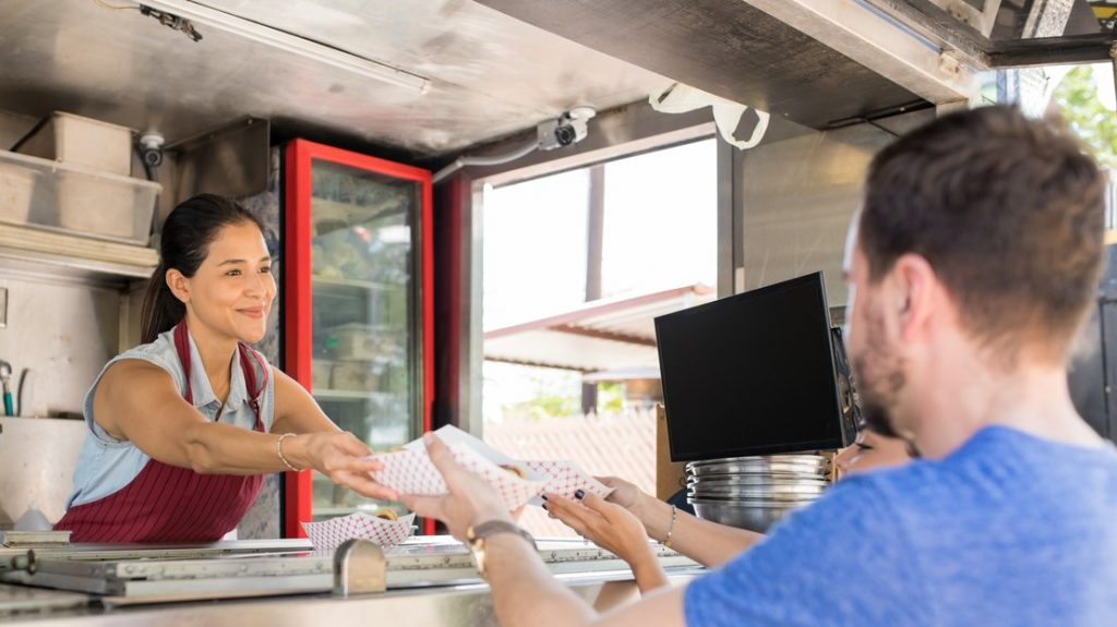 Cute young female cook selling hot dogs to a couple of customers in a food stand. Concept: how to start a food truck to expand your restaurant