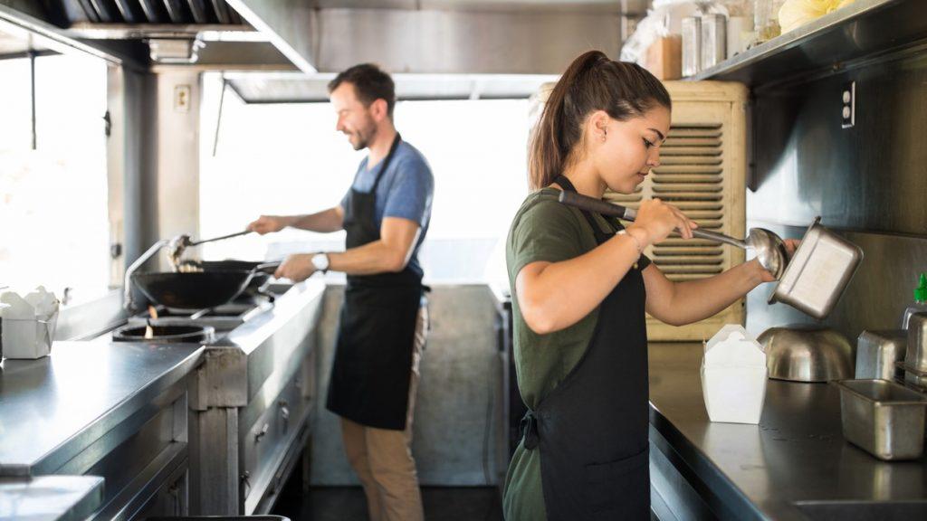 Dos personas cocinando y sirviendo comida dentro de la cocina de un food truck. Concept: cómo empezar un food truck para expandir tu restaurante