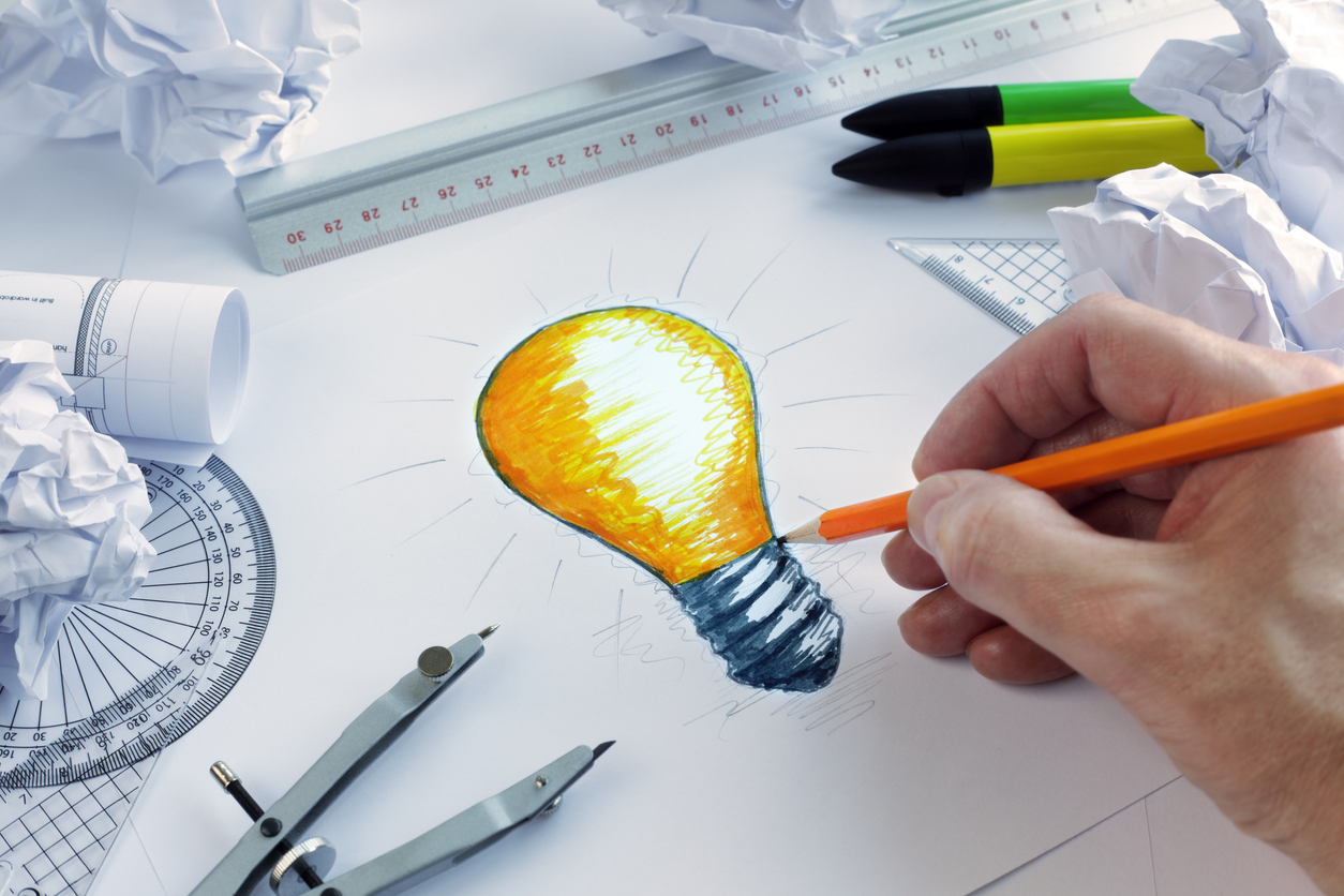 Designer drawing a light bulb, concept: creative advertising for your small business
